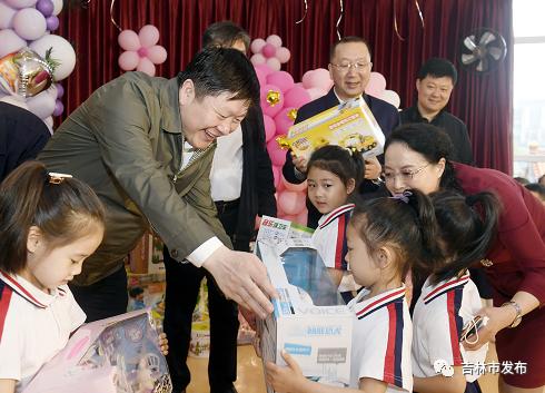 在吉林市妇联托幼中心,吉林市委书记贺志亮(左)向孩子们赠送节日礼物,表达节日的祝福