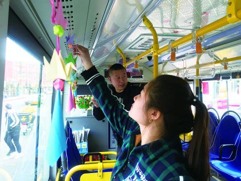 上图:市民郑微用亲手制作的千纸鹤布置公交车厢。