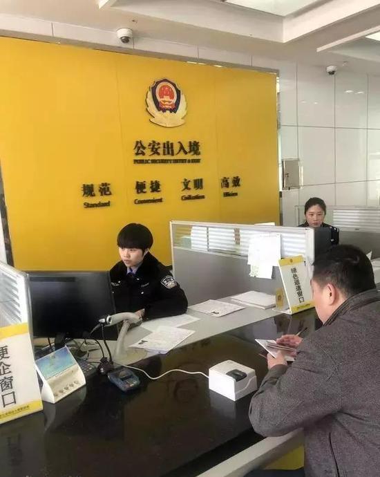 长春市公安局出入境服务大厅民警正在受理指导群众如何填表办证
