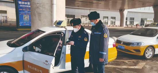 执法人员在机场对出租汽车例行检查。 丁莉 摄