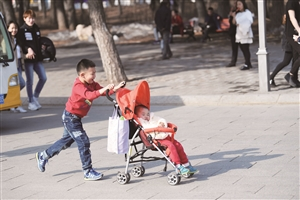 哥哥推着宝宝逛公园。