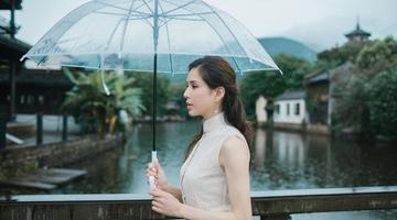 45岁李若彤穿淡雅长裙雨中漫步