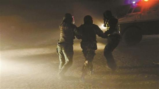 武警官兵帮被困者戴上头盔,在飞沙走石中将其引导至装甲车旁。 武警新疆总队克拉玛依支队 供图
