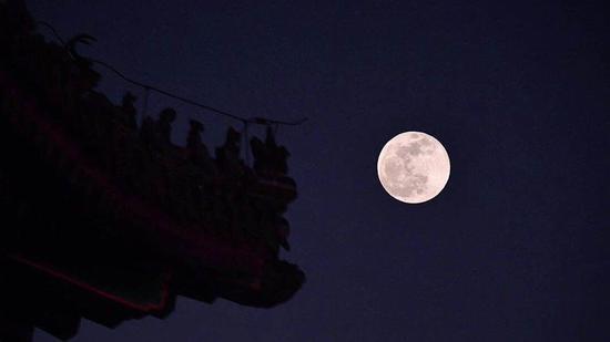"""1月21日 景山万春亭飞檐上的脊兽与""""超级月亮""""。摄影 / 新京报记者 李木易"""