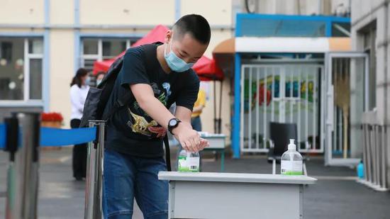吉林市第一实验小学学生进入校园后洗手。