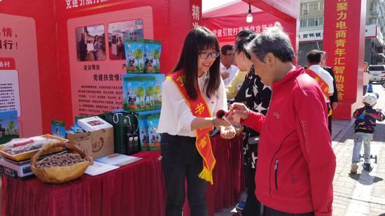 2018年9月,刘宇恒(左)在四平市第一书记代言展销会介绍榛子。