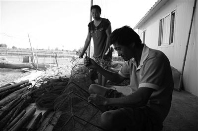 渔民正在织网等待恢复养殖。 薄云峰 摄