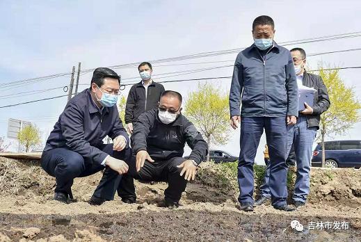 吉林市市长王路(左一)在丰满区旺起镇漂尔村水田地,查看春耕生产情况。