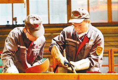中车长客高级技师李万君(右)和徒弟王善更在焊接轨道客车转向架。人民日报记者 赵树宴摄