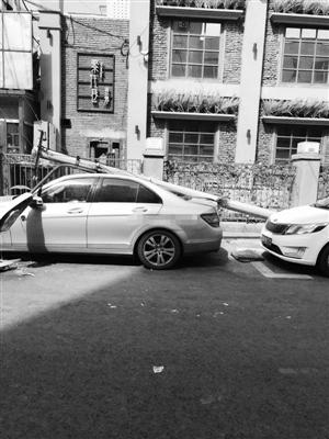 路灯杆被大风刮倒砸在车上。市民供图