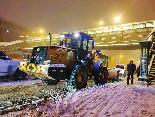 11月17日当晚,环卫部门正在使用机械清理主干道上的积雪。 刘颖摄