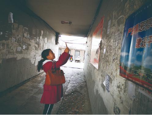 裴曼玲用手机拍下野广告上传到街道数字化管理平台。 林桂清 摄