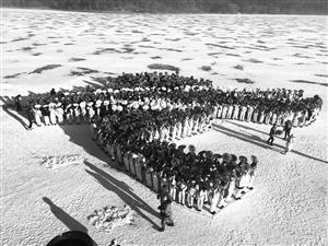 """学生们在雪地里拼组""""北京冬奥会会徽""""。"""