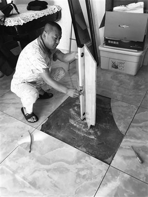 刘先生用水平尺测出瓷砖发生变形。 康重华 摄