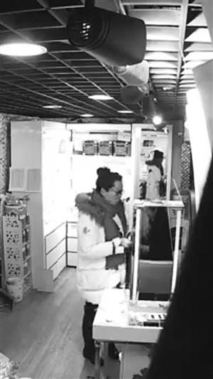 白衣女子拿着失主手机随后离开。市民供图