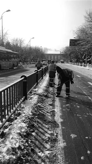 环卫工人正在清理积雪。本组摄影 于慧