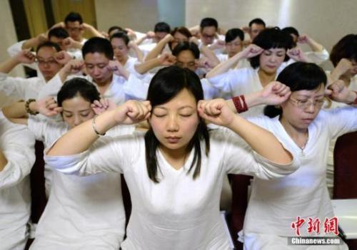 资料图:长沙首个睡眠班开课,学员们身穿白色睡衣做睡眠操。中新社发 杨华峰 摄