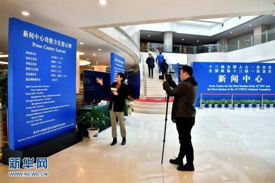 2月27日,两名记者在全国两会新闻中心内采访拍摄。新华社记者 李鑫 摄
