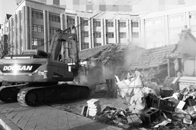 工作人员操作挖沟机对这处平房依法进行拆除。李子涵 摄