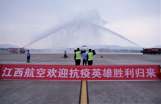 """↑机场举行""""过水门""""仪式,为江西省支援湖北随州医疗队""""接风洗尘""""。"""