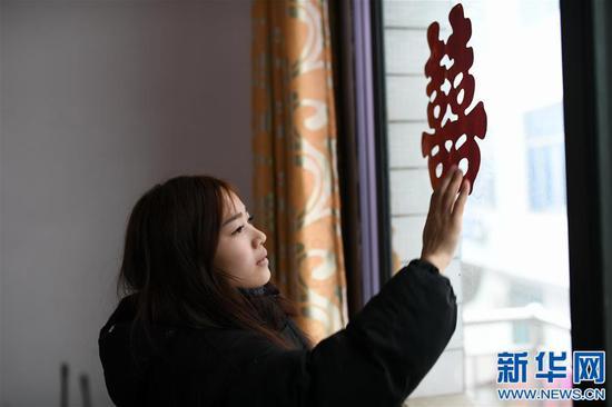黄林在装修一新的房间里贴上喜字(1月10日摄)。新华社记者 周密摄