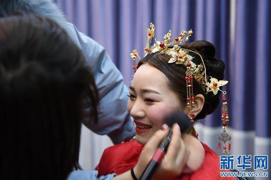 黄林在化妆时露出笑容(1月11日摄)。新华社记者 周密摄