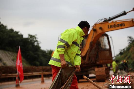 """应急抢险队一边用挖机清淤,一边安排工人在山凹处挖沟埋管引流,部分人员配合挖机铲除淤泥,采取""""人工+机械方式""""应急处置。 王俊摄"""