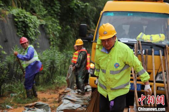 应急抢险队一边用挖机清淤,一边安排工人在山凹处挖沟埋管引流。 王俊摄