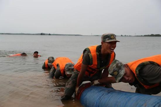 在三角联圩,官兵们勇敢跳入水中安装抽水泵