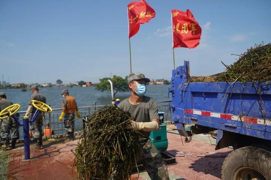 某合成旅官兵在三角乡帮助百姓清淤清垃圾。