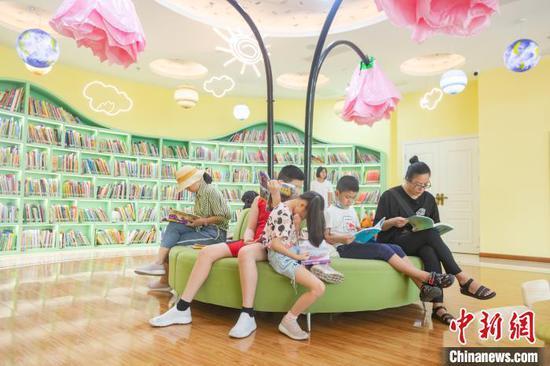 在江西省南昌市高新区图书馆的儿童阅读区内,不少儿童在阅读图书。 刘力鑫 摄