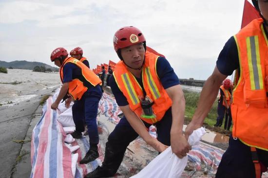 2020年7月,南昌市消防救援支队特勤大队50多名消防员顶着酷暑搬运7000多个沙袋,构筑了一条3公里的防线。图为南昌市新建区廿四联圩大堤抗洪抢险现场。
