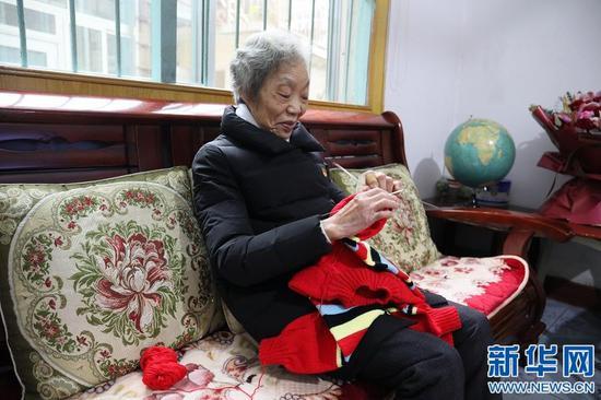 图为谢芝兰正在家中编织毛衣。新华网 王凯丰 摄