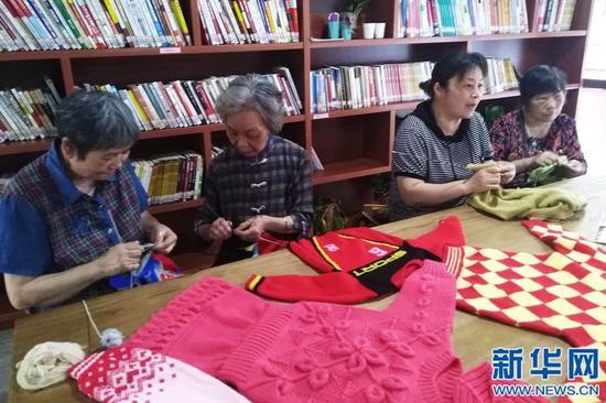 图为谢芝兰和社区居民一同编织毛衣。新华网发
