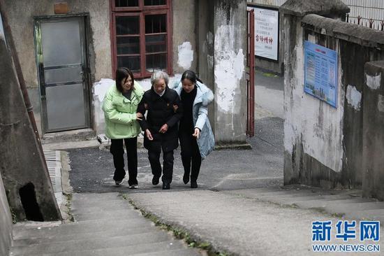 图为谢芝兰在社区工作人员搀扶下步行上坡。新华网 王凯丰 摄