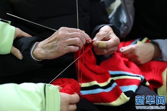 图为谢芝兰正在编织毛衣,手中棒针上下翻飞,动作娴熟。新华网 王凯丰 摄
