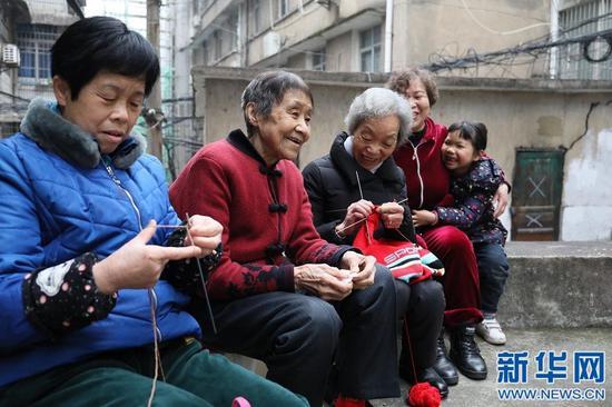 图为谢芝兰边和街坊邻居聊天边织毛衣。新华网 王凯丰 摄
