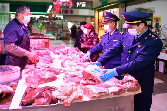 2021年2月5日,浙江省湖州市吴兴区市场监管局工作人员在农贸市场检查肉类(新华社记者黄宗治 摄)