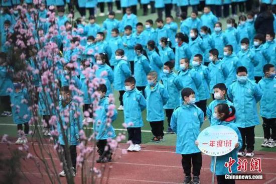 资料图:重庆市大渡口区双山实验小学的学生们戴着口罩保持间隔进行开学典礼。中新社记者 陈超 摄