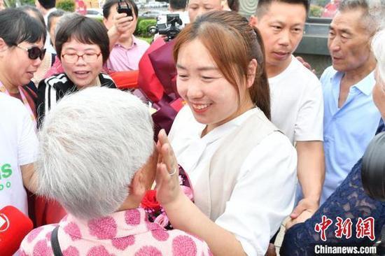 焦阳在现场认亲,用手轻抚白发苍苍的外婆的脸颊。 樊哲平 摄