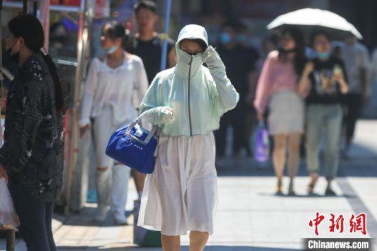 """江西南昌""""秋老虎""""发威,市民全副武装应对高温天气。 刘力鑫 摄"""