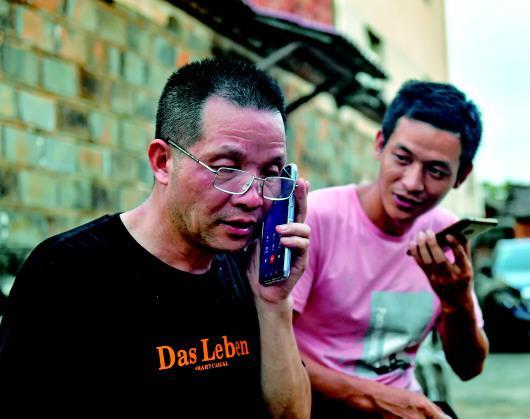 8月6日,张玉环在和自己的儿子学习用智能手机通话。 新华社记者 胡晨欢 摄