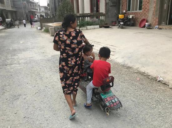 吴爱梅带着两个孩子去领物资