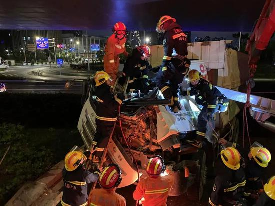 7月27日20时,南昌西湖区生米大桥下抚生南路,一辆沙土车撞倒限高杆导致驾驶员被困驾驶室内。图为八一消防救援站第一时间派出14名消防员展开救援。图为救援现场。