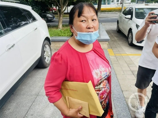 9月9日,江西南昌,劳荣枝案一审宣判后,被害人小木匠的妻子朱大红手中的文件袋里装着判决书。摄影/上游新闻记者 时婷婷
