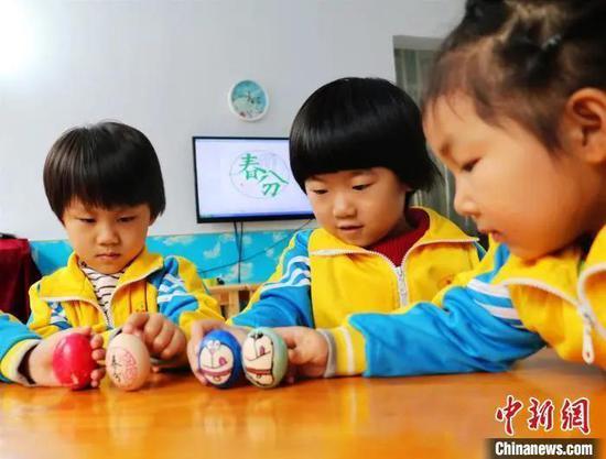 """资料图:河北平乡县直第一幼儿园的孩子们玩起""""立蛋""""游戏,感受春分的文化情趣。姚友谅 摄"""