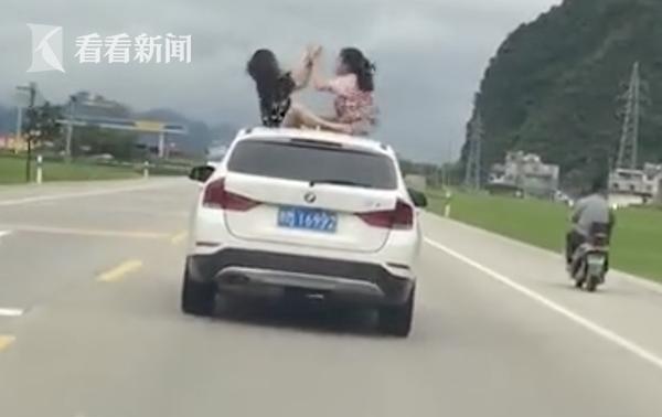 俩女孩坐行驶的宝马车顶猜拳嬉戏:太热了透透气