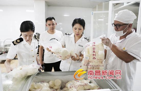 执法人员对南昌师范附属实验小学(玉泉岛校区)食堂的食品生产厂家、生产日期进行检查