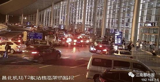 (昌北国际机场航站楼前高架桥上网约车扎堆停放)