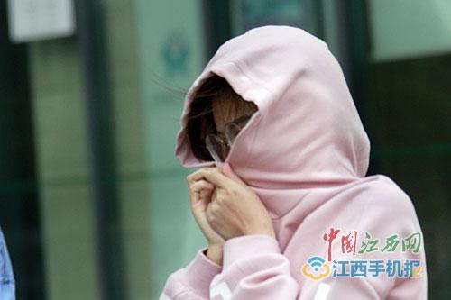 风中紧紧抓住帽子的女子图/江南都市报全媒体记者徐国亮